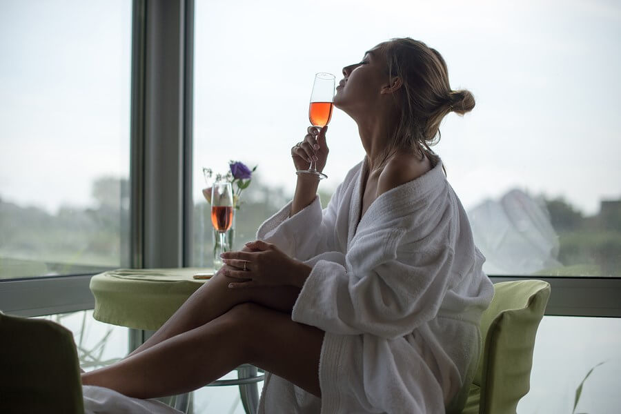 A bath-robed woman enjoying a sensuous glass of amazing Celebrity Wines!