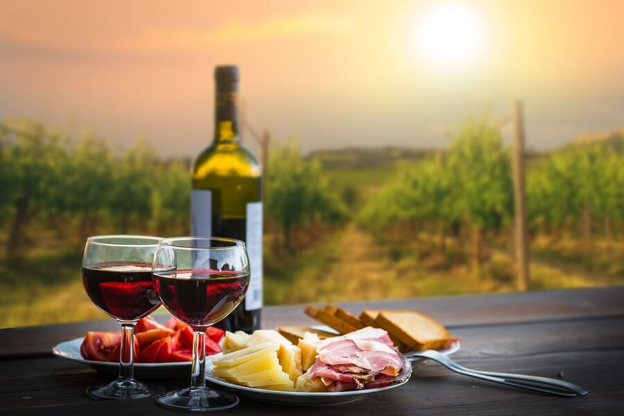 A sumptuous display of a simple meal at sunset with 2 wine glasses and a bottle of plum wine!