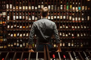 A man looking over an amazing selection of wine bottles!