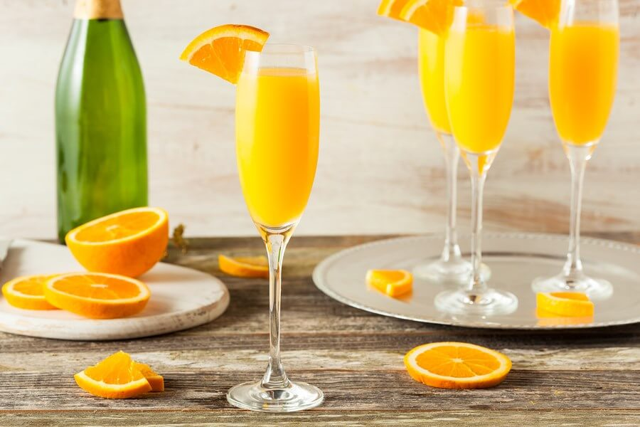 A beautiful display of Brunch Mimosas on a table with oranges for garnish and an empty bottle of champagne in the background!