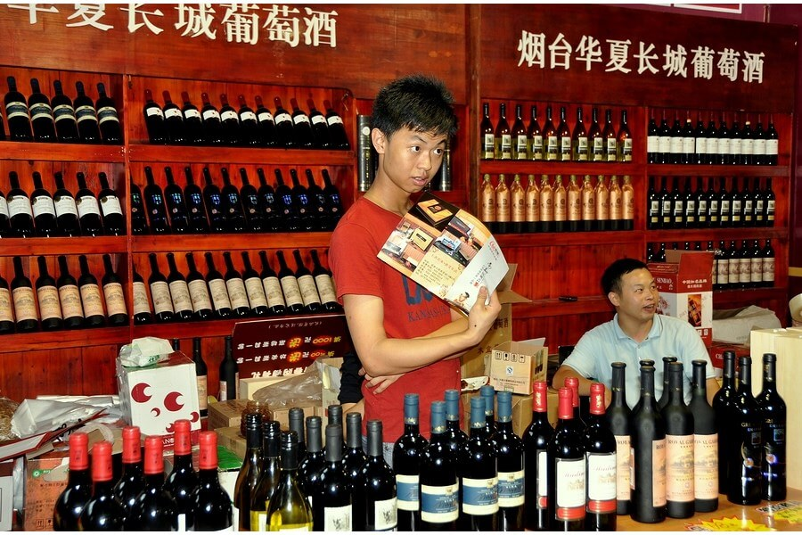 A Chinese vendor selling amazing Chinese Wine! Bottles of Chinese Wine being displayed in the forefront and background!
