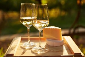 2 beautiful glasses of pinot blanc wine in the sunlight, on a board with amazing cheeses, ready to be drunk and eaten!