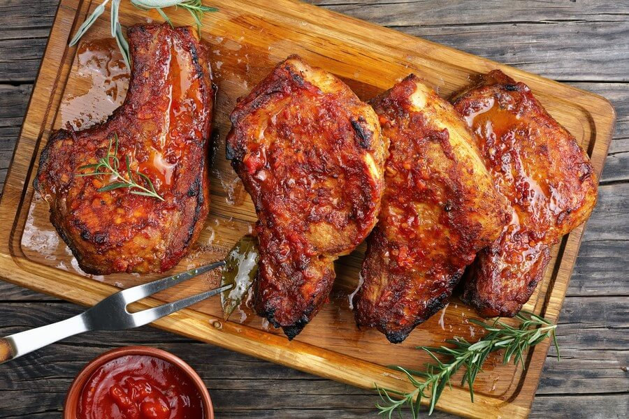 Beautifully caramelized pork chops, on a wooden cutting board with rosemary, barbecue utensils, and a bowl of sauce