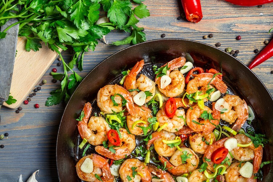 Delicious shrimp prepared in a cast iron skillet, waiting to be added to pasta and cream sauce for Shrimp Scampi!