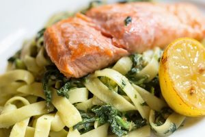 Beautifully cooked, flaky salmon sitting luxuriously atop a bed of herbed fettuccine, with a baked half lemon