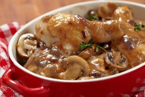 A delicious red handled bowl filled with delicious mushroom wine sauce slow cooked chicken!