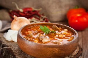 A wooden bowl of Southwestern Turkey soup,on a backdrop of garlic, onion, chili and tomatoes.