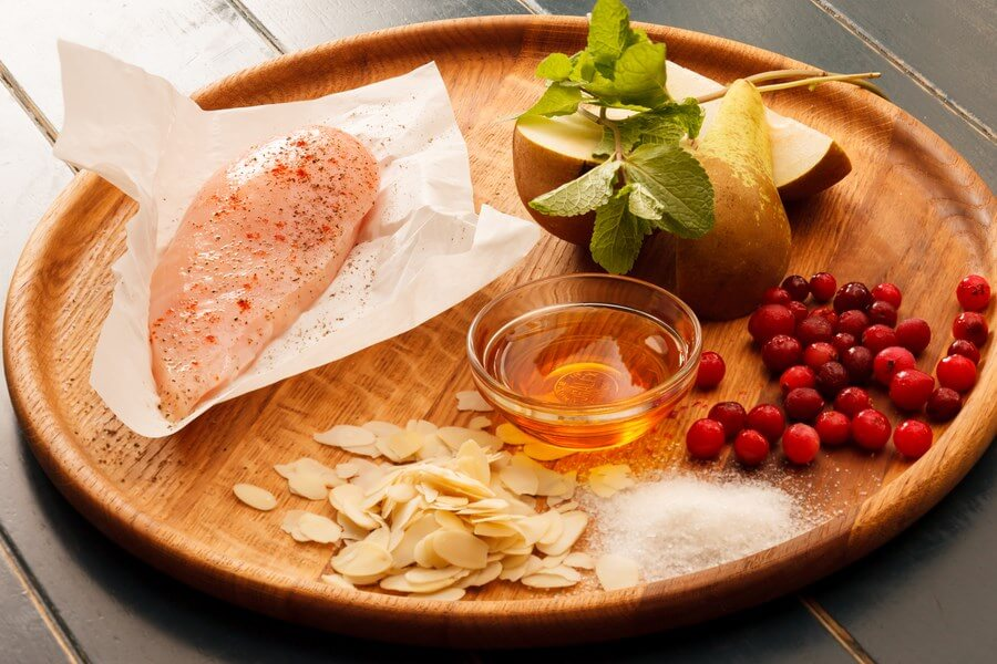Chicken, almonds, cranberries, pear, salt, honey and mint on a wooden board; ready to be prepared.