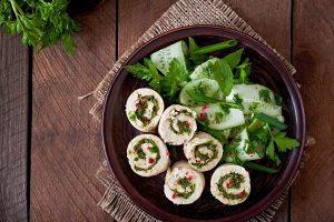 Deliciously prepared turkey roll ups with leaves for garnish, on a wooden table!