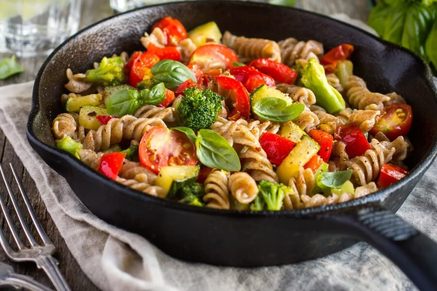 Amazing cold pasta salad, with tomatoes, broccoli, and more! Garnished with basil leaves.