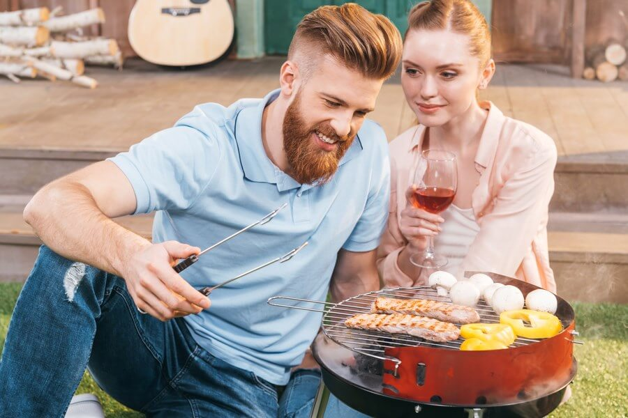 Barbecue Wine Pairing - A beautiful couple grilling meat and vegetables in their backyard with wine!