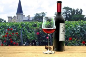 Rare Wines - A beautiful rare vintage of wine served on an oak table in a beautiful vineyard, with flowers blooming!