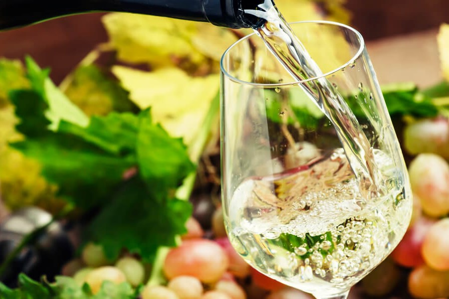 Riesling Wine - A beautifully clear Riesling wine being poured wonderfully into a wine glass on a backdrop of fruit!