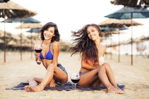 2 beautiful fit young women on the beach enjoying boxed wine USA style.