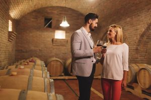 A pair of wine drinkers enjoy their wine tasting experience within a beautiful wine cellar!