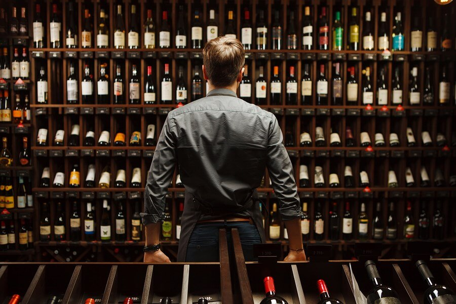 A man staring at a wall of amazing wines, looking for Cheap Wine Deals!