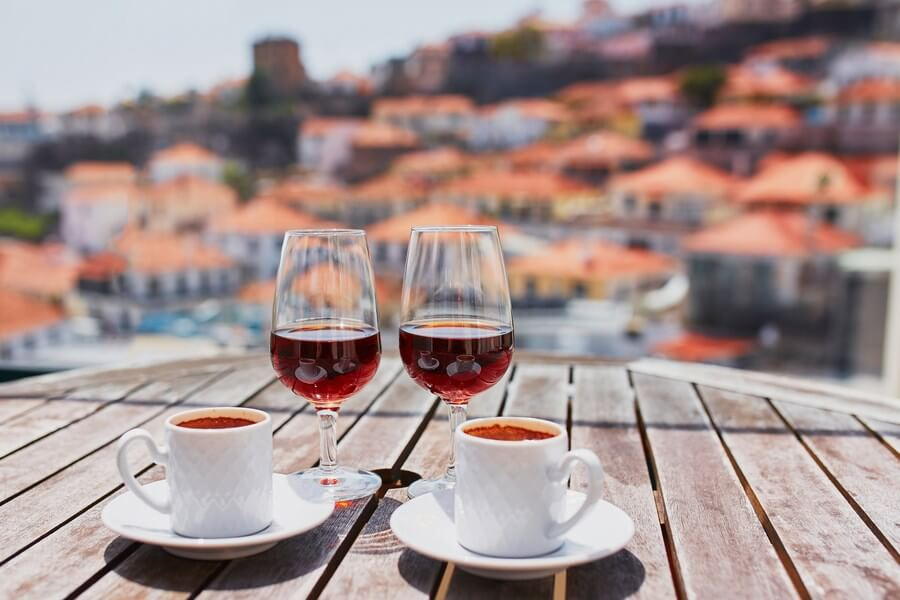 2 small glasses of espresso in the fore, with 2 sparkling glasses of Madeira wine in the Spanish sun!
