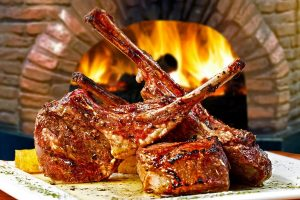 Beautiful honey wine glazed lamb ribs with fire place in the background.