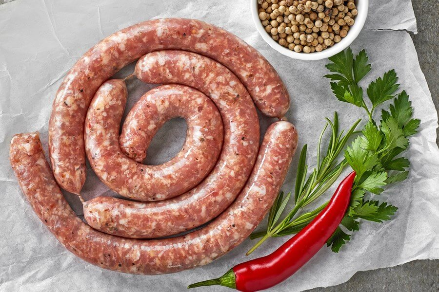 Sumptuous, Delicious Italian pork sausages, with a bowl a coriander seeds, parsley, and red chili pepper